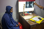 An Orthopedic surgeon examines an x-ray report of Taniya Akhter's broken ankle, one of the migrated workers. The son of the Saudi employer pushed her from the balcony when she refused to do sex with him. Dhaka, Bangladesh. Taniya went to Saudi Arabia to work as a home maid but within a month she became the target of the son of the employer and assaulted regularly.