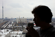 Moscow, Russia, 31/03/2012..Woman drinking coffee in  the Planet Cosmos restaurant on the 25th floor of the Hotel Cosmos with panoramic views of Moscow behind.