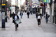 People wearing face masks walk along the shopping district Oxford Street which is largely empty of shoppers as the national coronavirus lockdown three continues on 28th January 2021 in London, United Kingdom. Following the surge in cases over the Winter including a new UK variant of Covid-19, this nationwide lockdown advises all citizens to follow the message to stay at home, protect the NHS and save lives.