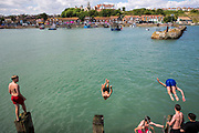 Young people dive jumping off Folkestone Harbour into the sea water after the annual Trawler race and fun day in Folkestone, Kent, England, United Kingdom.