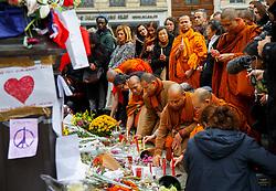 © Licensed to London News Pictures. 16/11/2015. Paris, France. Buddhist monks visit a memorial outside Bataclan Cafe in Paris, France following the Paris terror attacks on Monday, 16 November 2015. Photo credit: Tolga Akmen/LNP