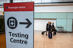 """© Licensed to London News Pictures. 24/11/2020. London, UK. Flight attendants walk past a Covid testing centre sign at London Heathrow Terminal 5 today. Minister for Transport Grant Shapps has announced that quarantine for air travellers will drop to 5 days from mid December if they take a private Covid test. Under the new """"test to release"""" scheme passengers who test negative after 5 days self-isolation will be able to carry on with their normal lives. Photo credit: Alex Lentati/LNP"""