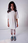 An individual child wearing a white t-shirt, with a sad, lonely, hurt, afraid, worried  or depressed expression.