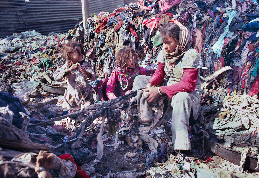 Coptic Christian Community in Cairo, Egypt home to the zabbaline who have the hereditary rights to pick up trash in Cairo.  Rag picking children sort clothes for recycling.