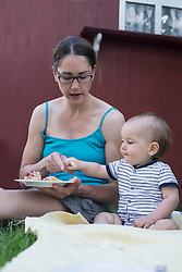Baby boy grabbing the fork from his mother's plate in lawn, Munich, Bavaria, Germany