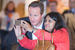© Licensed to London News Pictures . 30/09/2014 . Birmingham , UK . A woman stops DAVID CAMERON to pose for a selfie as he arrives at the LBC stand this morning for an interview with Nick Ferrari . The 2014 Conservative Party Conference in Birmingham . Photo credit : Joel Goodman/LNP