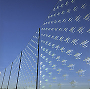'Counting the Cost' is a memorial sculpture in glass designed by Renato Niemis which is outside at the American Air Museum at the Imperial War Museum, RAF Duxford, England. The sculpture comprises of 52 toughened clear float glass panels, each etched with the outlines of 7,031 aircraft missing in action in operations flown by American air forces (Air Force and Navy Groups) from Britain during the Second World War. The images are scaled at 1:240, diagonally pointing towards the blue summer sky once filled with bombers and fighters during the air campaign over Germany and France. Picture from the 'Plane Pictures' project, a celebration of aviation aesthetics and flying culture, 100 years after the Wright brothers first 12 seconds/120 feet powered flight at Kitty Hawk,1903. .