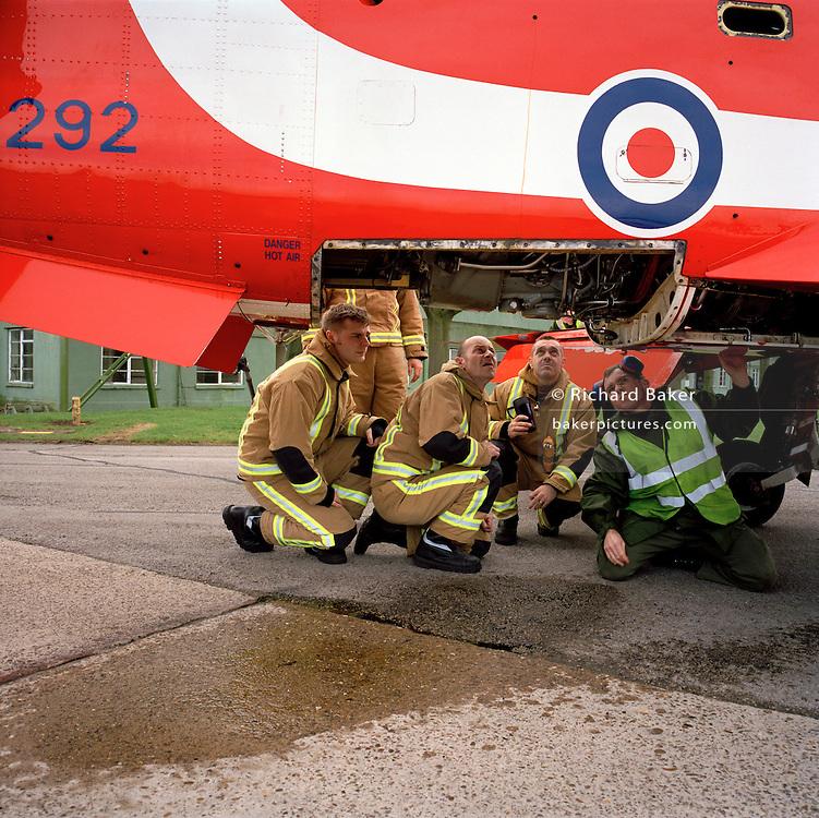 RAF ground crew teaches local civilian firemen about 'Red Arrows', Royal Air Force aerobatic team Hawk jet.