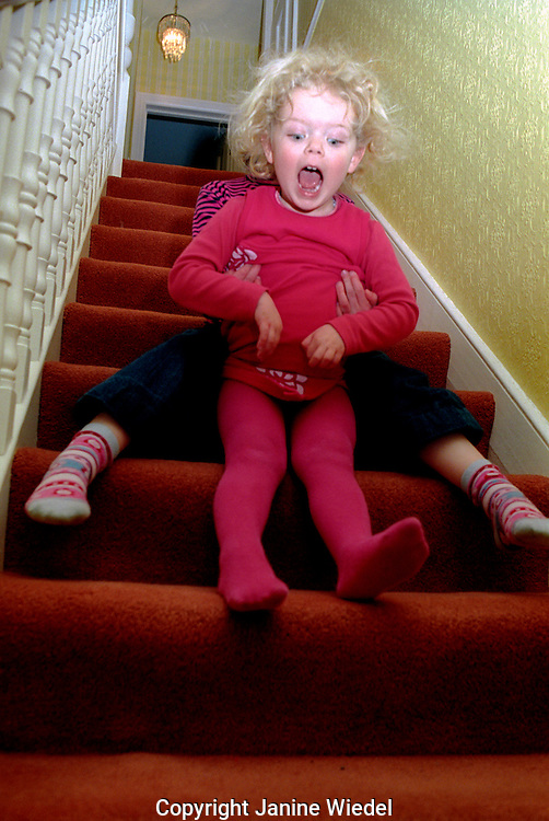 Young children playing on stairs in hallway of their home.