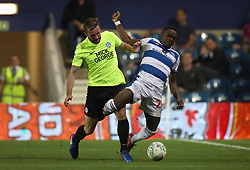 Peterborough's Jason Naismith (left) and Queens Park Rangers' Bright Osayi-Samuel battle for the ball during the Carabao Cup, First Round match at Loftus Road, London.