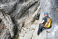 Local mountain guide on the steep via ferrata route to the source of the river Soca, in the Trenta Valley, Triglav National Park, Slovenia. © Rudolf Abraham