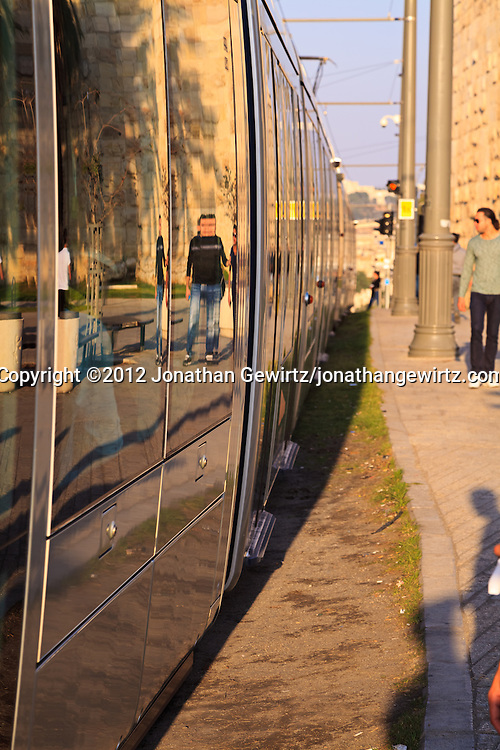 A train in Jerusalem's light rail system on Sultan Suleiman Street along the walls of the Old City of Jerusalem. WATERMARKS WILL NOT APPEAR ON PRINTS OR LICENSED IMAGES.