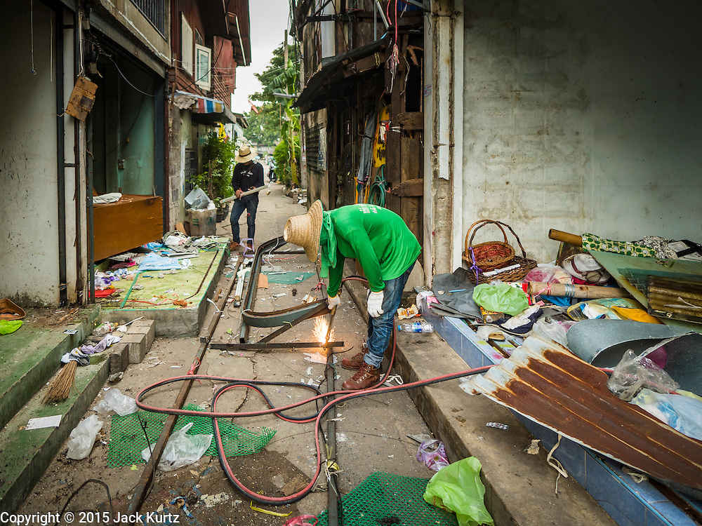 16 NOVEMBER 2015 - BANGKOK, THAILAND:   A demolition worker uses a cutting torch to take apart a home in the Wat Kalayanamit neighborhood. Fifty-four homes around Wat Kalayanamit, a historic Buddhist temple on the Chao Phraya River in the Thonburi section of Bangkok, are being razed and the residents evicted to make way for new development at the temple. The abbot of the temple said he was evicting the residents, who have lived on the temple grounds for generations, because their homes are unsafe and because he wants to improve the temple grounds. The evictions are a part of a Bangkok trend, especially along the Chao Phraya River and BTS light rail lines. Low income people are being evicted from their long time homes to make way for urban renewal.          PHOTO BY JACK KURTZ