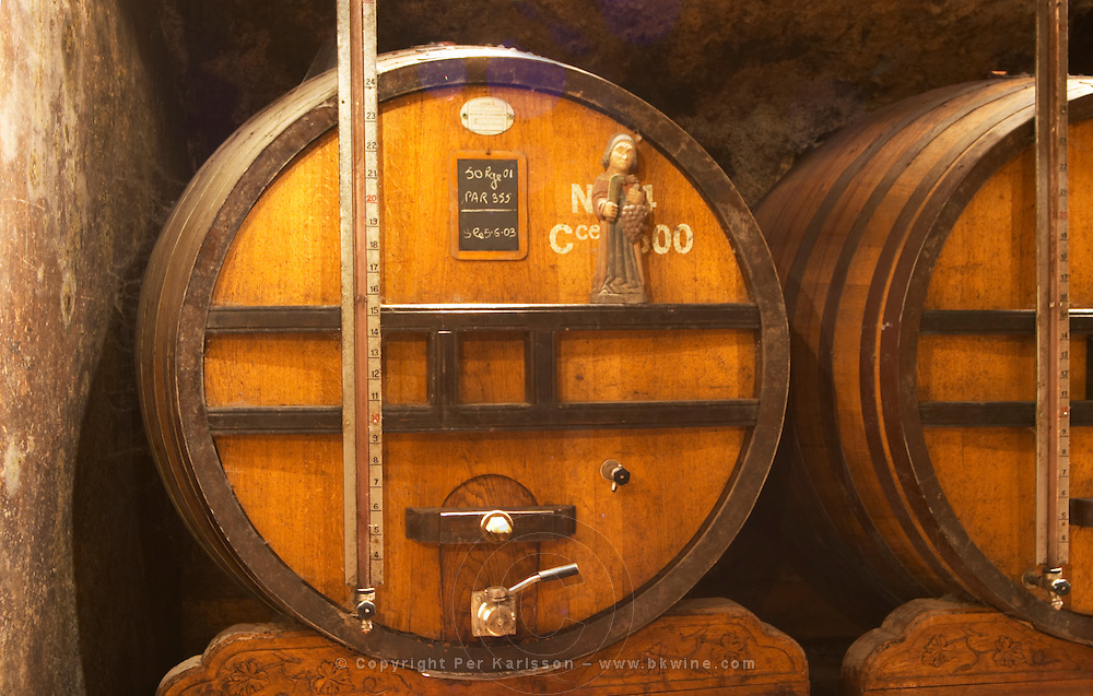 Wooden vats with aging wine in the cellar of Guigal in Ampuis. A measuring coloumn that shows how much wine is in the barrel and a small statuette of a monk harvesting wine  Domaine E Guigal, Ampuis, Cote Rotie, Rhone, France, Europe
