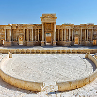 Palmyra. Syria. View of the 2nd century theatre which laid buried under sand up until the 1950's and has since been largely excavated and restored back to its former glory. The magnificent sumptuous adorned stage has a large central door known as the Royal Gate, which is flanked by two smaller ones. Facing the stage is the semi-circle orchestra; 20 metre is diameter and beyond it rises the cavea with its nine rows of seats. It is though that originally the cavea was thirty rows of seats in three storeys.