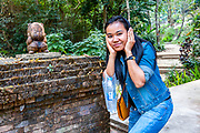 Beautiful Asian girl poses next to a small statue at an ancient temple above Chiang Mai. Photo Release: Yes