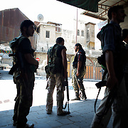 August 10, 2012 - Aleppo, Syria: A group of Free Syria Army (FSA) fighters take position one street away from government's army men in Babar Nassar, a small neighborhood in the old citadel of Aleppo...The Syrian Army have in the past week increased their attacks on residential neighborhoods where Free Syria Army rebel fights have their positions in Syria's commercial capital, Aleppo. (Paulo Nunes dos Santos/Polaris)