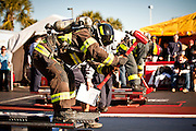 Two firefighters slam a sledgehammer into a steel beam wearing full firefighting gear and working against the clock during the international finals of the Firefighter Combat Challenge on November 18, 2011 in Myrtle Beach, South Carolina.