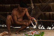 Huaorani Indian - Tage Kaiga making feather crown. Gabaro Community. Yasuni National Park.<br /> Amazon rainforest, ECUADOR.  South America<br /> The crowns are made from a split vine and feathers from various birds such as toucans, parrots and macaws are glued on with heated bees wax.<br /> This Indian tribe were basically uncontacted until 1956 when missionaries from the Summer Institute of Linguistics made contact with them. However there are still some groups from the tribe that remain uncontacted.  They are known as the Tagaeri & Taromanani. Traditionally these Indians were very hostile and killed many people who tried to enter into their territory. Their territory is in the Yasuni National Park which is now also being exploited for oil.