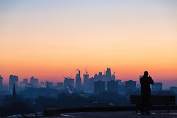 London, December 12 2017. A walker photographs the skyline before the sun rises on a clear very cold morning in London, seen from Primrose Hill in Camden. © Paul Davey