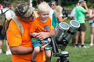 Middletown, New York - A young boy gets ready to look at the partial solar eclipse through binoculars with solar filters on Alumni Green at SUNY Orange on Aug. 21, 2017.