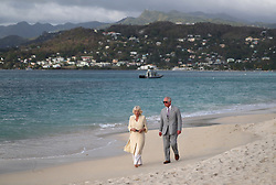 The Prince of Wales and the Duchess of Cornwall walk along a beach during a one day visit to the Caribbean island of Grenada.