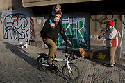 As a man cycles downhill with a child on his shoulders, a local lady takes her morning walk with her dogs along Kostelni street in Holesovice district, Prague 7, on 20th March, 2018, in Prague, the Czech Republic.