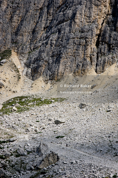 Hikers from Passo Falzarega (Pass) ascend the lower slopes of Tofana di Mezzo (3,244 m), a Dolomites mountain in south Tyrol, Italy.