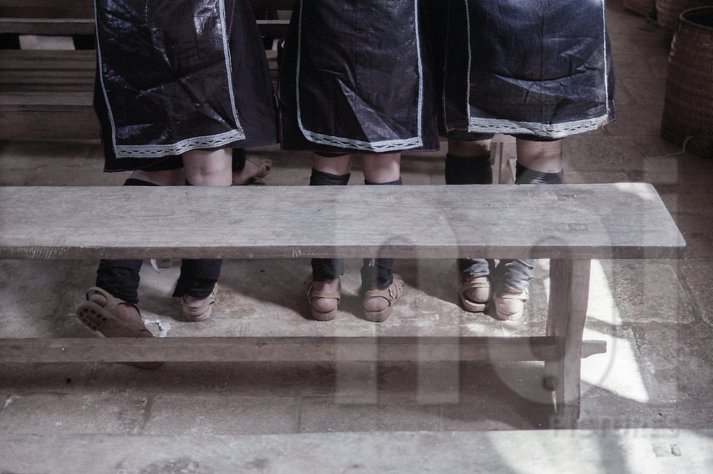 Lower body picture of Hmong girls wearing traditional outfit and plastic sandals during a mass in Sapa's church. Vietnam, Asia