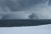 Stormy winter view across Nappstraumen towards mountains of Vestvågøy, Lofoten Islands, Norway