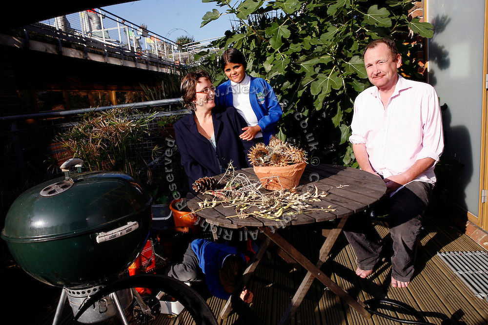 Naomi Martin, 43, (left) and Simon Courage, 43, are portrayed in front of their house in BedZED with their children Claudia, 10, (centre) and Louis,4,  on Thursday, Sep. 6, 2007, in London, UK. BedZED or the Beddington Zero Energy Development, is an environmentally-friendly housing development near Wallington, England in the London Borough of Sutton. It was designed by the architect Bill Dunster who was looking for a more sustainable way of building housing in urban areas in partnership between the BioRegional Development Group and the Peabody Trust. There are 82 houses, 17 apartments and 1,405 square meters of work space were built between 2000. The project was shortlisted for the Stirling Prize in 2003. The project is designed to use only energy from renewable source generated on site. In addition to 777 square meters of solar panels, tree waste is used for heating and electricity. The houses face south to take advantage of solar gain, are triple glazed and have high thermal insulation while most rain water is collected and reused. Appliances are chosen to be water efficient and use recycled water wherever possible. Low impact building materials were selected from renewable or recycled sources and were all originating within a 35 mile radius of the site to minimize the energy required for transportation. Also, refuse collection facilities are designed to support recycling and the site encourage eco-friendly transport: electric and LPG cars have priority over petrol/diesel cars, and electricity is provided by parking spaces appositely built for charging electric cars.