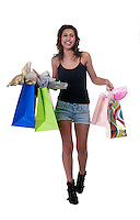 Young hispanic woman walking with shopping bags very happy.
