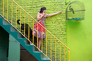 An Argentinian woman with her dog and bird against a bright green wall.