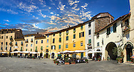 Buildings surrounding the Piazza dell'Anfiteatro inside the ancinet Roman ampitheatre of Lucca, Tunscany, Italy . Piazza dell'Anfiteatro is a public square in the northeast quadrant of walled center of Lucca. The ring of buildings surrounding the square, follows the elliptical shape of the former second century Roman amphitheater of Lucca. The square can be reached through four gateways located at the four vertices of the ellipse. A cross is carved into the central tile of the square with the arms pointing to the four gateways of the square. The base of the former amphitheater  dating back to the 1st or 2nd century BC, at its peak had about 18 rows of amphitheater seats held some 10,000 spectators.<br /> <br /> Visit our ITALY HISTORIC PLACES PHOTO COLLECTION for more   photos of Italy to download or buy as prints https://funkystock.photoshelter.com/gallery-collection/2b-Pictures-Images-of-Italy-Photos-of-Italian-Historic-Landmark-Sites/C0000qxA2zGFjd_k<br /> .<br /> <br /> Visit our ROMAN ART & HISTORIC SITES PHOTO COLLECTIONS for more photos to download or buy as wall art prints https://funkystock.photoshelter.com/gallery-collection/The-Romans-Art-Artefacts-Antiquities-Historic-Sites-Pictures-Images/C0000r2uLJJo9_s0 .<br /> <br /> If you prefer to buy from our ALAMY PHOTO LIBRARY  Collection visit : https://www.alamy.com/portfolio/paul-williams-funkystock/lucca.html .