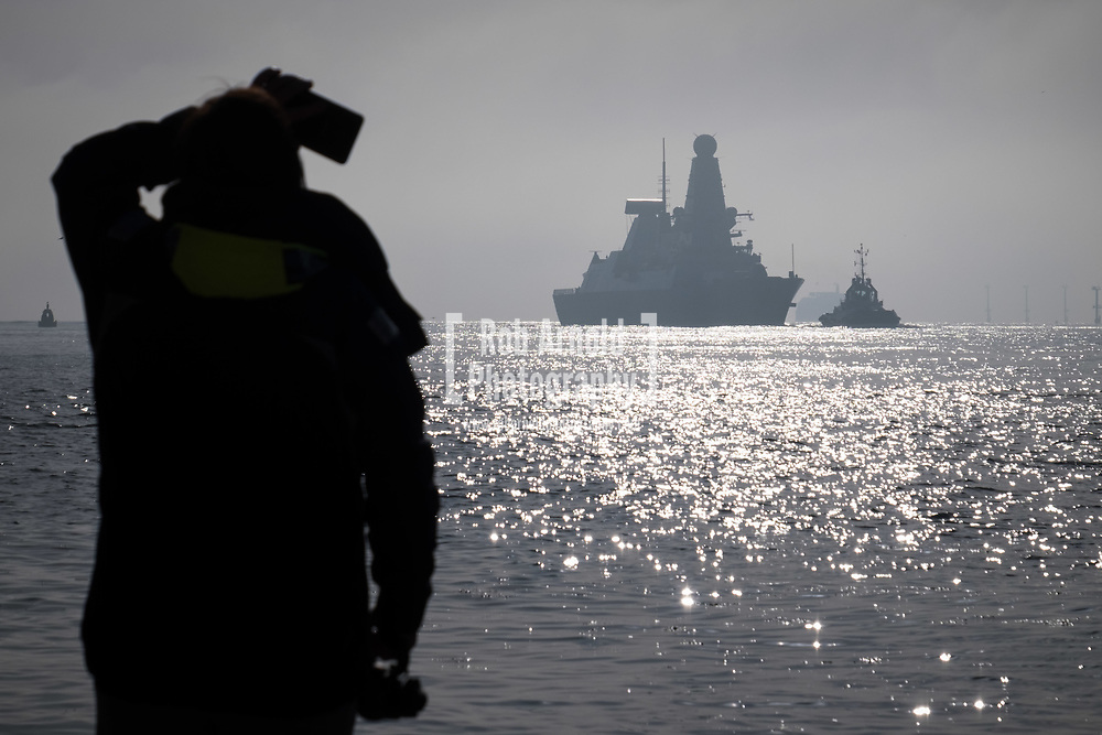 A woman watching as HMS Dragon sails into her home port of Portsmouth for the first time in two months.  The Type 45 destroyer has been on a deployment involving exercises with the U.S. Navy and also a visit to the British Overseas Territory of Gibraltar.