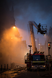 © Licensed to London News Pictures . 13/07/2013 . Manchester , UK . More than 60 fire fighters tackle a blaze at a shop on Oldham Street in Manchester City Centre in which a fireman died. Twelve crews from four stations are battling the blaze which started in a store room in Paul 's Hair World.  Photo credit : Joel Goodman/LNP