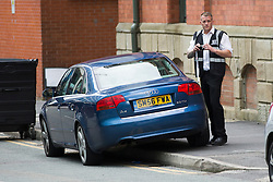 © Licensed to London News Pictures. 21/06/2016. Manchester UK. Picture shows a ES Parking Enforcement employe believed to be working on behalf on Manchester city council parking his own unmarked Audi up a kerb & on double yellow lines on Left Bank in Manchester before photographing other vehicles parked illegally who could later receive a fine. Photo credit: Andrew McCaren/LNP