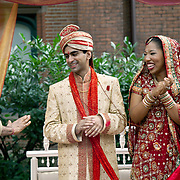 Indian groom and African-Korean bride have fun during their outdoor Hindu wedding ceremony