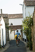 France, Ile de Re (island), and village of Les Portes, located on the Atlantic coast, off shore from La Rochelle. Jacques Sourisseau riding an old bicycle through a small lane, while carrying a surboard.