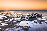 A sunset at Masirah Island during sea lows tide.<br /> An island off the east coast of mainland Oman in the Arabian Sea, and the largest island of the country. It is 95 km long north-south, between 12 and 14 km wide.
