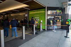 "© Licensed to London News Pictures. 07/03/2021. LONDON, UK.  Customers line up outside the new 2,500 sq ft Amazon Fresh store in Ealing, west London on its first weekend of opening. It is the first ""just walk out"" grocery store in the UK and the first outside the USA.  As a ""contactless"" shop, it is available to anyone signed up to Amazon and with the app on their smartphone.  In-store cameras and artificial intelligence monitor customers picking up items who simply walk out and billing takes place later automatically.  Photo credit: Stephen Chung/LNP"
