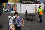 Street portrait caricatures and construction artwork faces in Leicester Square in central London. The selling of cartoon faces of the rich and famous is known throughout the world as well as a five-minute portrait session for a tourist sitter. But in the background are more cartoon-esque faces on a construction hoarding as a Wesminster council street sweeper pushes his barrow across the scene, just as a young boy walks past the caricature faces.
