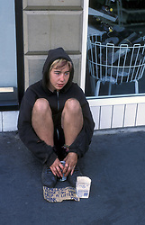 Young homeless woman begging on street UK