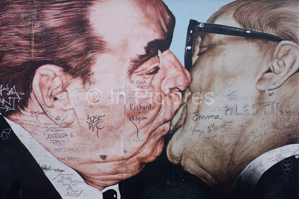 A detail from the oversized artwork entitled Brotherhood Kiss (Bruderkuss) by Dmitry Vrubel that once adorned a section of the notorious Berlin Wall in western Germany Russian. The two men are kissing on the lips, one of the most iconic paintings that symbolised a divided Europe during the Cold War. The Communist Soviet leader Leonid Brezhnev kisses his East German (DDR) counterpart Erich Honecker, which was ultimately copied on to coffee cups and T-shirts across the world before being destroyed by the authorities. The artist was angry but he says he will paint a new image which was derived from a photograph of the two leaders taken 1979 but became a potent symbol of Communism's corruption and ultimate failure.