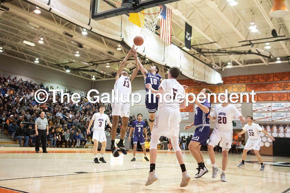 Sandia Prep's Matt Leach (13) and Clovis' Josiah Lombrana (10) reach for a rebound Saturday night at the Gallup Invitational boys basketball tournament at Gallup High School.