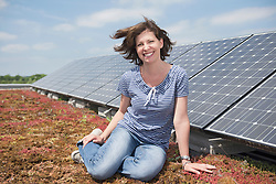 Portrait young woman in front of solar panel