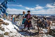 Tsaatan reindeer herders leading their reindeer (Rangifer tarandus) around an ovoo, a sacred pile of stones, Khovsgol Province, Mongolia