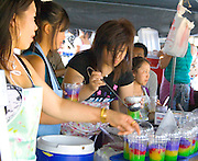 Attractive teenage Hmong SE Asian women fill cups with fruit drink. Hmong Sports Festival McMurray Field St Paul Minnesota USA