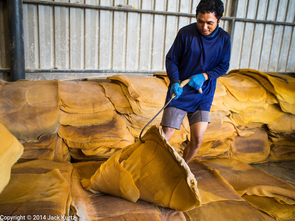 """15 DECEMBER 2014 - CHUM SAENG, RAYONG, THAILAND: A worker stacks rubber sheets at a business that buys rubber from farmers in Chum Saeng, Thailand. Thailand is the second leading rubber exporter in the world. In the last two years, the price paid to rubber farmers has plunged from approximately 190 Baht per kilo (about $6.10 US) to 45 Baht per kilo (about $1.20 US). It costs about 65 Baht per kilo to produce rubber ($2.05 US). Prices have plunged 5 percent since September, when rubber was about 52Baht per kilo. Some rubber farmers have taken jobs in the construction trade or in Bangkok to provide for their families during the slump. The Thai government recently announced a """"Rubber Fund"""" to assist small farm owners but said prices won't rebound until production is cut and world demand for rubber picks up.     PHOTO BY JACK KURTZ"""