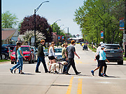 """03 MAY 2020 - PELLA, IOWA: People cross Washington Street, the main street in downtown Pella, Iowa. Traffic was close to normal in Pella Sunday, three days after the town's businesses were allowed to reopen. Pella is a small community in central Iowa. The town's economy is driven by tourism and the Tulip Festival, the largest tourist event of the year, has already by canceled for 2020 because of fears that the festival could become a COVID-19 (Coronavirus/SARS-CoV-2) """"Super Spreader"""". The Governor of Iowa reopened 77 of Iowa's 99 counties. The counties that were reopened have reported low incidences of Coronavirus. Marion County, where Pella is located, has reported 12 cases of Coronavirus. There have been 9,169 confirmed cases of Coronavirus in Iowa, including 1,476 cases in the Des Moines area, less than one hour away. Many people from Des Moines drove to Pella this weekend to see the tulips for which the town is famous.     PHOTO BY JACK KURTZ"""